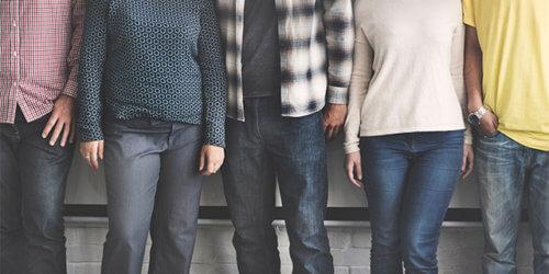 Fotografi på fem anonyma personer som står på rad. Huvud och fötter är bortbeskurna, blandning mellan kön och etnicitet