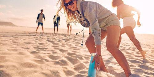 Fotografi på fyra unga vuxna som umgås på stranden. En kvinna är i fokus och hon plockar upp en blå EauBottle från sanden.