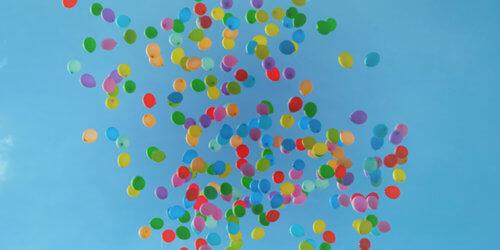 Mångfärgade ballonger som stiger mot en blå himmel