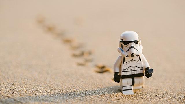 Fotografi på en legofigur i form av en Stormtrooper som går genom ett ökenlandskap med fotspår som försvinner bort i oskärpa bakom figuren i sanden.