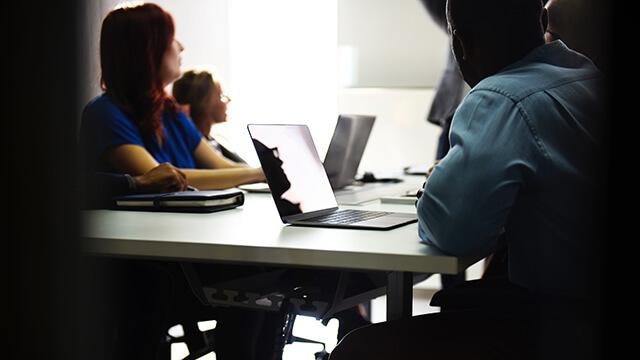 Fotografi på personer som sitter i ett möte med laptops kring ett bord, vända bort från kameran mot ett gemensamt fokus.