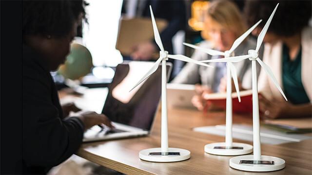 Personer som sitter och arbetar vid ett träbord. I fokus på bordet står tre vita vindkraftverk i modellstorlek