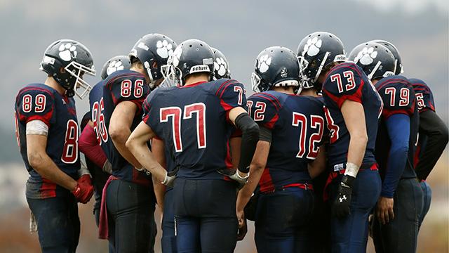 Fotografi på ett amerikanskt fotbollslag som pratar taktik i en klunga.