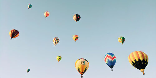 Fotografi upp mot en ljusblå himmel med ett flertal luftballonger som stiger mot nya höjder.