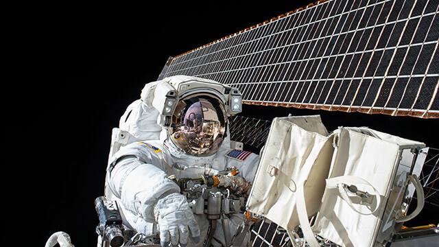 Fotografi från NASA på en astronaut som utför arbete vid ett par solpaneler ute i rymden.