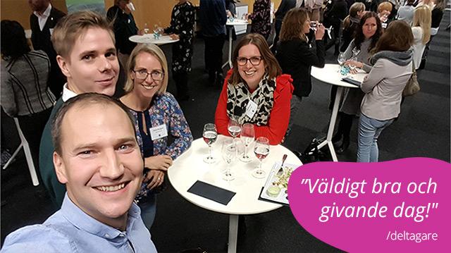 """Fotografi från konferenstillfället med Simon och några deltagare samlade kring ett ståbord, de har just ätit lunch. Nere i högra hörnet finns ett deltagarcitat på en rosa bakgrundsplatta """"Väldigt bra och givande dag!""""."""