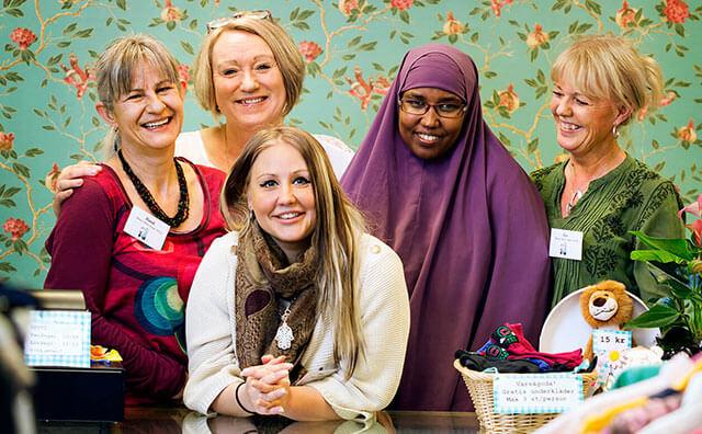 Fotografi Framtidens hållbarhetsrapport 2015 på fem kvinnor som står vid en butiksdisk, de flesta tittar in i kameran, alla ler.