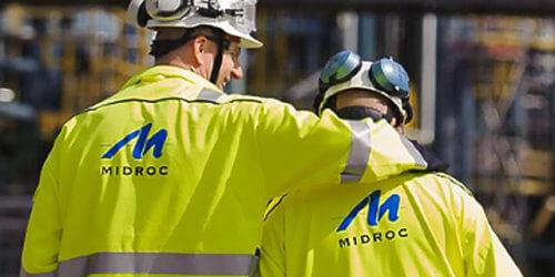 Fotografi på två av Midrocs medarbetare med arbetskläder och säkerhetsutrustning. Den högra mannen håller om axeln på sin kollega medan de går framåt, ansiktet vänt mot honom och ler.
