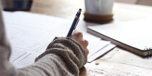 Närbild på en persons arm och hand när denne sitter och skriver på papper som ligger på bordet. I den ljusa bakgrunden syns ett skrivblock och en kaffekopp.
