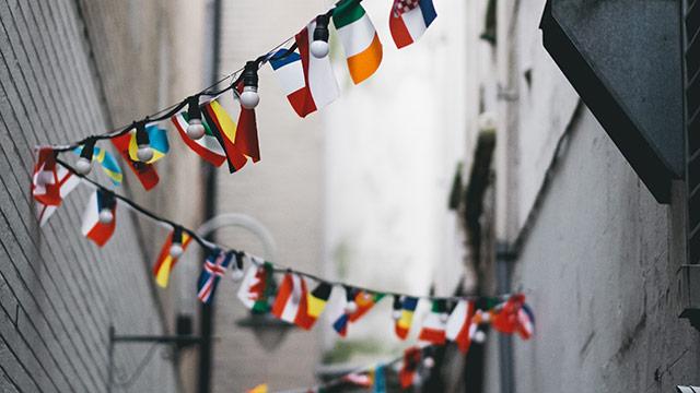 Fotografi vinklat uppåt i en gränd där vimplar med olika nationers flaggor vajar på en lina som sicksackar mellan husväggarna.