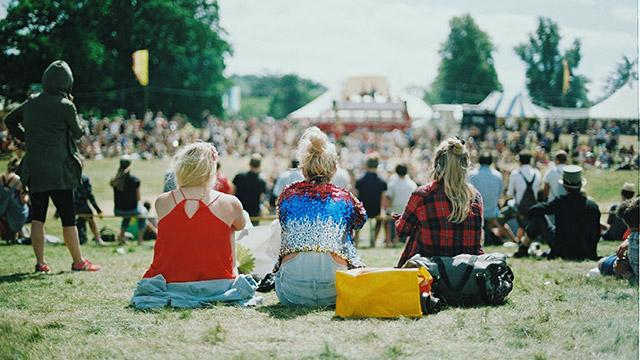 Fotografi från ett festivalområde dagstid. I fokus sitter tre unga kvinnor på gräset med ryggarna mot fotografen, blickandes mot en scen en bit bort som syns i bakgrunden tillsammans med ett folkhav.