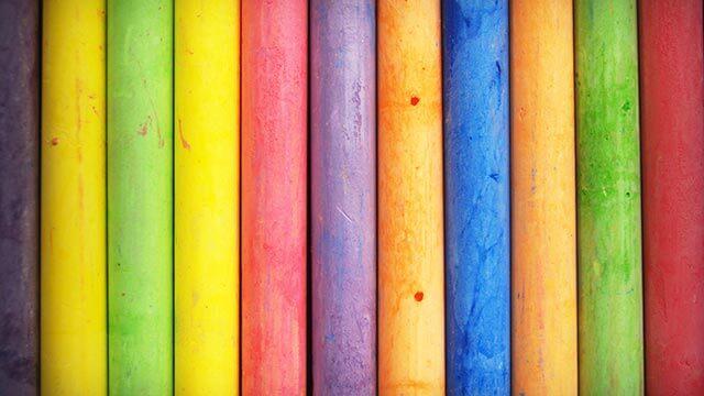 Abstrakt fotografi på en mångfärgad trävägg. Färger som förekommer är gult, grönt, blått, orange, rött och lila.