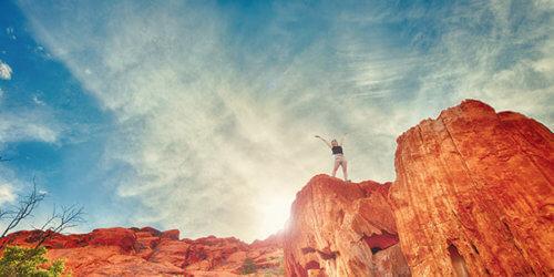 Fotografi på en kvinna som står högt uppe på en röd bergsklippa med solen strålandes i ryggen och uppsträckta armar mot skyn.