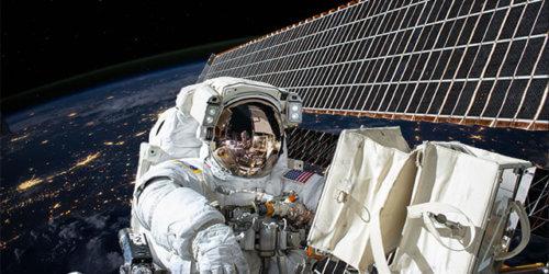 Bild på en astronaut som arbetar på en rymdstation med jorden i bakgrunden.
