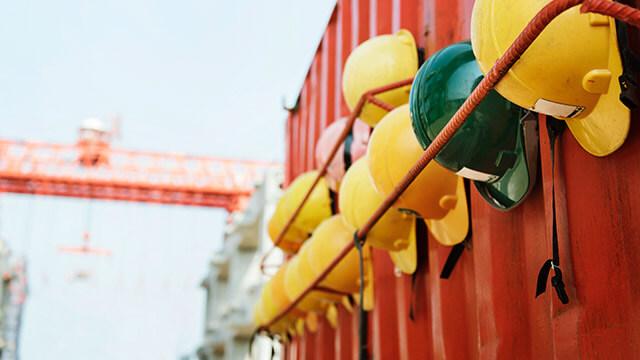 Skyddshjälmar hängandes på en röd container, i bakgrunden syns en hamnkran