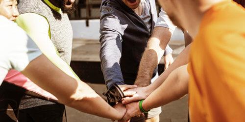 Fotografi på åtta individer i träningskläder som samlas i en handcirkel och hejar-rop.