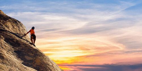 Fotografi på en kvinnlig bergsklättrare mot en morgonfärgad himmel och sol