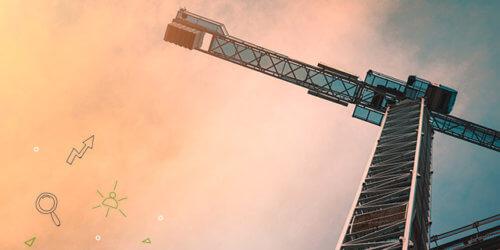 Fotografi underifrån en byggkran mot en morgonglödande himmel.