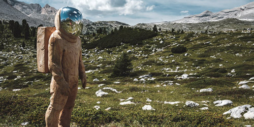 En trädstaty i form av en astronaut med ett speglande visir, ståendes i på en bergsslätt.