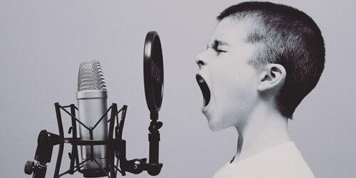 Svartvitt fotografi på en pojke som skriker in i en mikrofon.