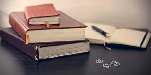 Fotografi på böcker liggandes på ett bord. Tre på hög och en öppnad i bakgrunden. Tre illustrerade vita gem i förgrunden.