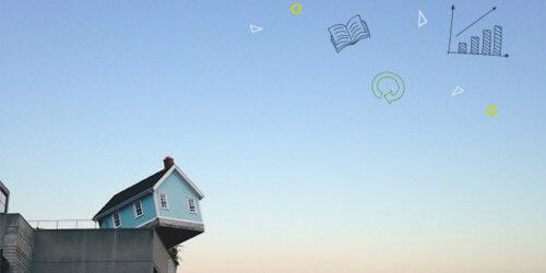 Fotografi på ett litet blått hus som står på kanten av en betongbyggnads tak mot en ljus morgonhimmel.