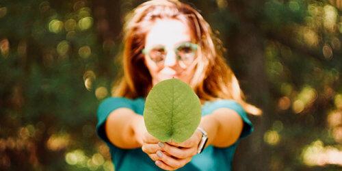 Kvinna som håller upp ett grönt blad mot kameran. Bladet är i fokus medan hon och en skog är suddiga i bakgrunden.