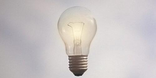 Fotografi på en tänd, svävande glödlampa mot en gråblå bakgrund.