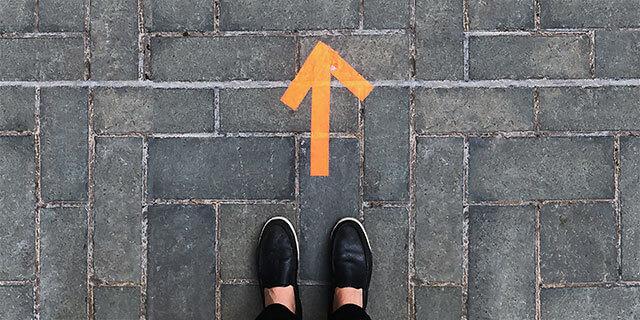 Fotografi ovanifrån på en stenbelagd gata med en orange pil tejpad och ett par skor ståendes i pilens riktning.
